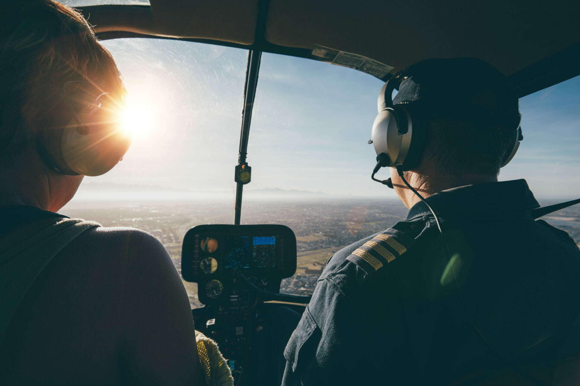 Two pilots in a helicopter flying on a sunny day